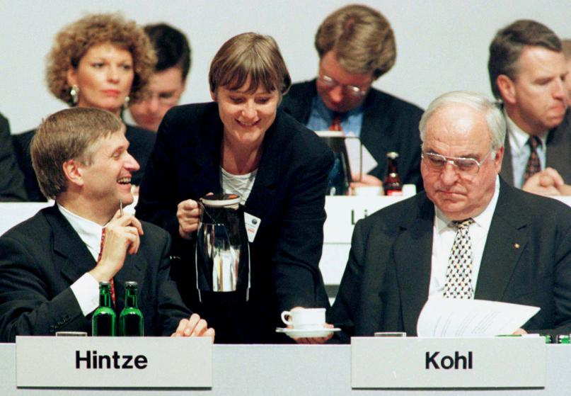 Министр по делам окружающей среды Ангела Меркель (в центре) наливает кофе канцлеру Германии и председателю ХДС Гельмуту Колю (справа) и секретарю ХДС Питеру Хинтце (слева) на ежегодной партийной конференции Христианско-демократического союза 21 октября 1996 года.
