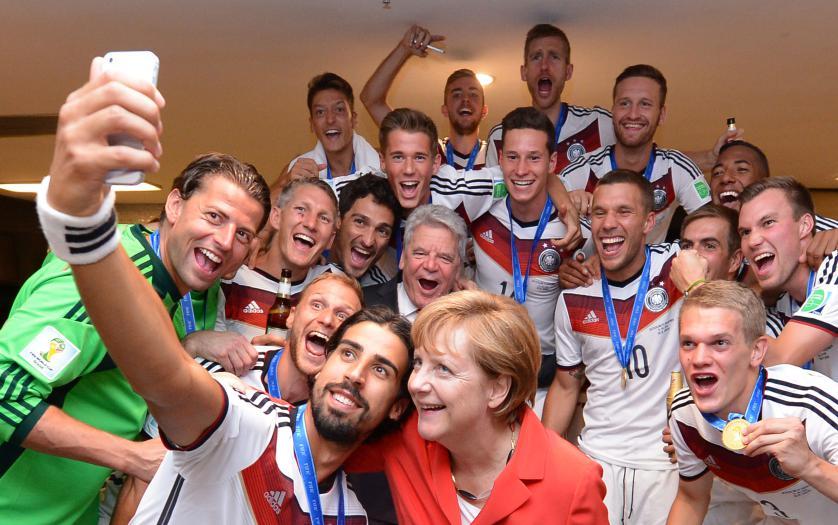 Канцлер Ангела Меркель и президент Германии Йоахим Гаук празднуют вместе с игроками в раздевалке национальной сборной после финального матча Чемпионата мира по футболу FIFA в Бразилии, где Германия играла с Аргентиной в Рио-де-Жанейро 13 июля 2014 года.