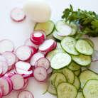 Нарезать редис, огурцы и яйца кружками, выложить в салатник.